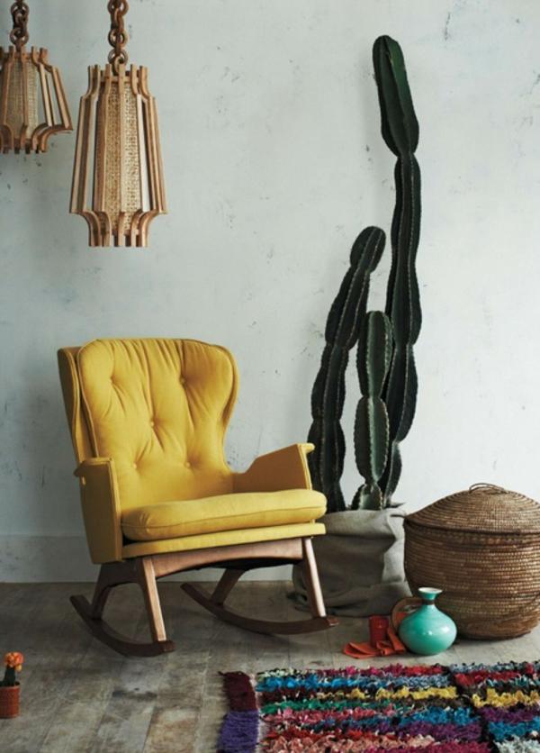 großer-kaktus-neben-einem-gelben-sessel- eine weiße wand dahinter