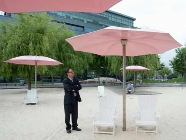ein mann steht unter rosigen hochwertigen sonnenschirmen am strand