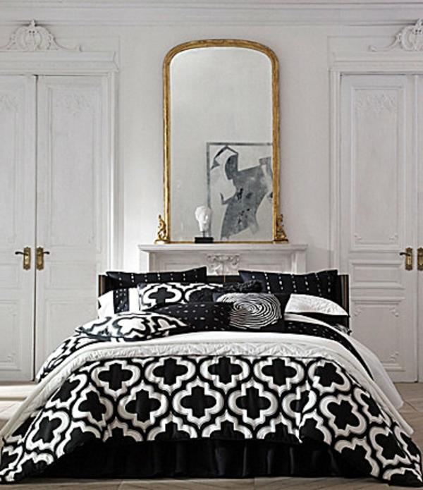 moderne-schwarze-bettwäsche-mit-weißen-elementen- und einem riesigen spiegel