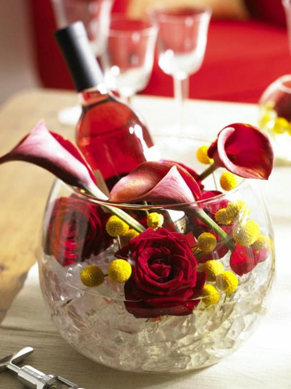 moderne-und-elegante-sommerliche-tischdeko- weinflasche und rosen in einem kugelförmigen becher