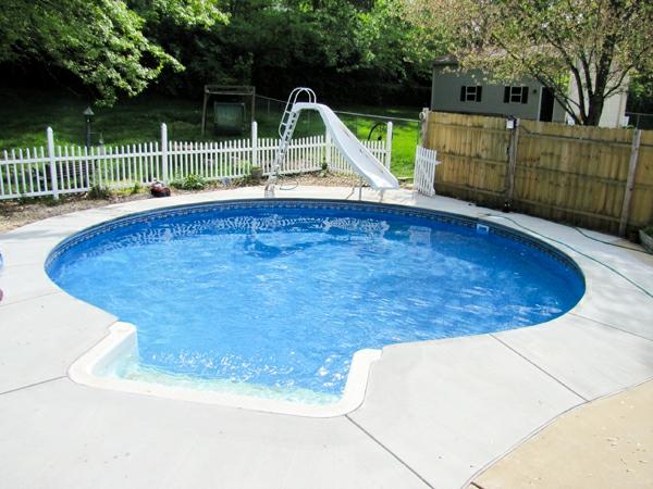 moderner-pool-mit-interessanter-form- daneben ist eine rutsche