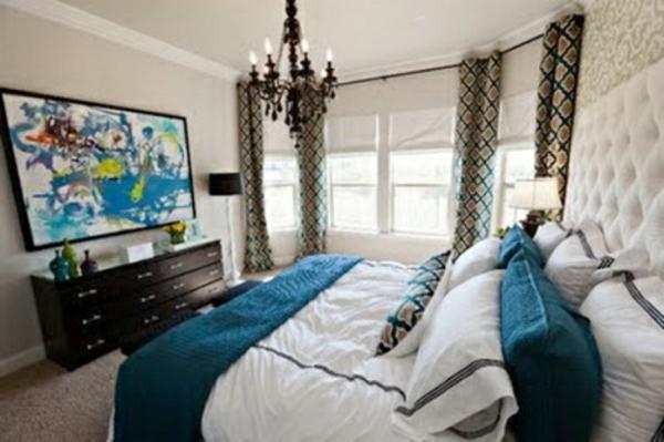 modernes-schlafzimmer-mit-origineller-fensergestaltung und einem großen bett mit vielen kissen