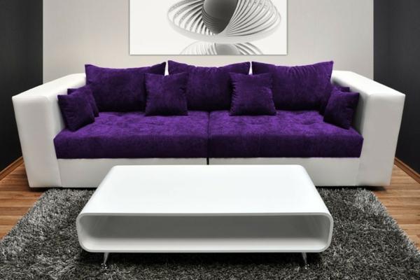modernes-weißes-lila-sofa-mit-sofakissen-in-lila-farbe- ein großes bild an der wand
