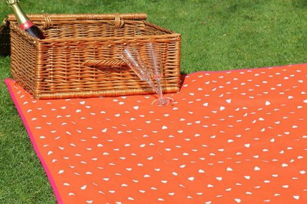 orange-picknick-decke- und ein korb darauf