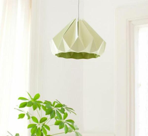 origami-lampenschirm-im-grün-und-die-pflanze-neben-der-weisse-wand