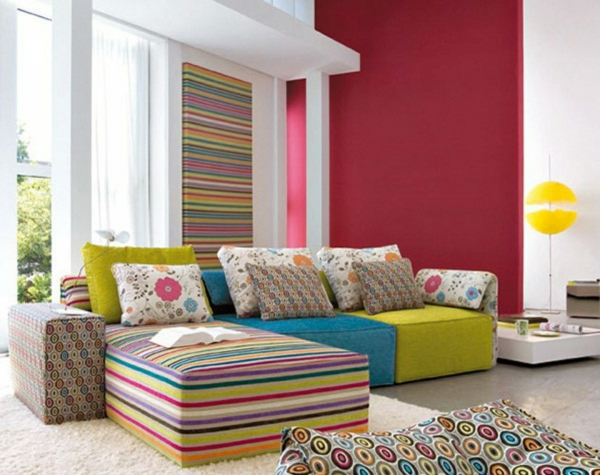 schicke-rote-akzentwant-sofa-auf-bunten-streifen-weiße-wände