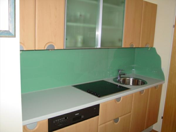 schöne-küchenrückwand-aus-glas-mit-interessanter-farbe- schränke aus holz