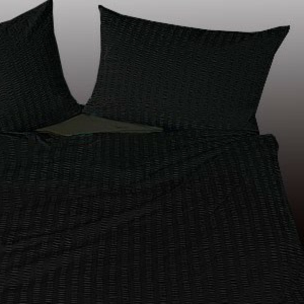 schwarze-bettwäsche- und kissen auf einem bett