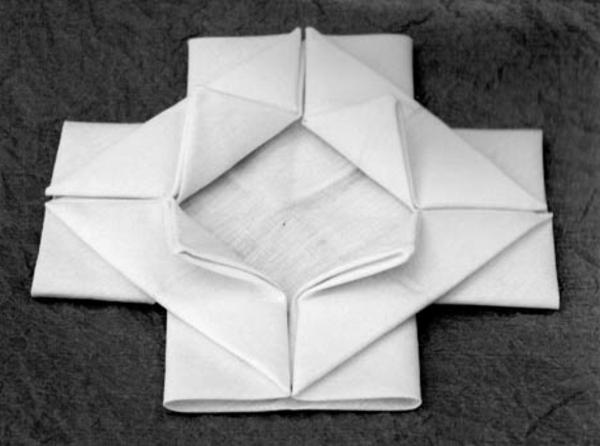 serviette-falten-weiße-rose-schaffen-hintergrund in grau