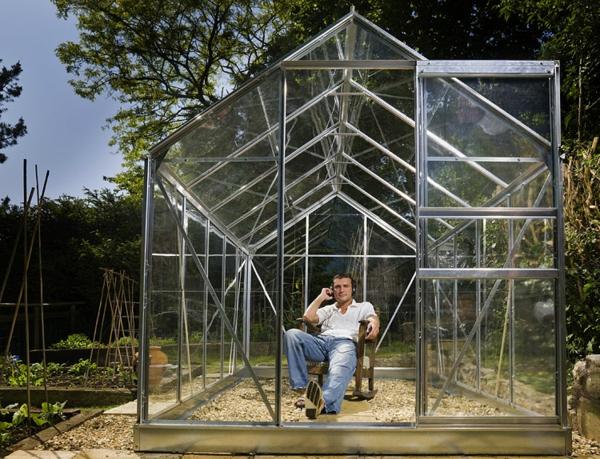 super-aussehendes-modernes-glashaus-ein man sitzt auf einem stuhl
