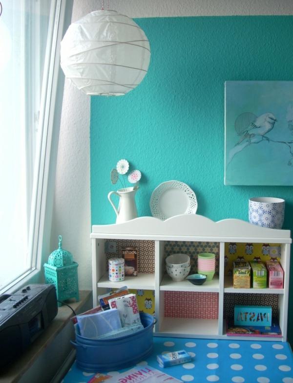türkis-wohnraum-blauen-teppich-auf weißen-kreisen-weißer-kronleuchter