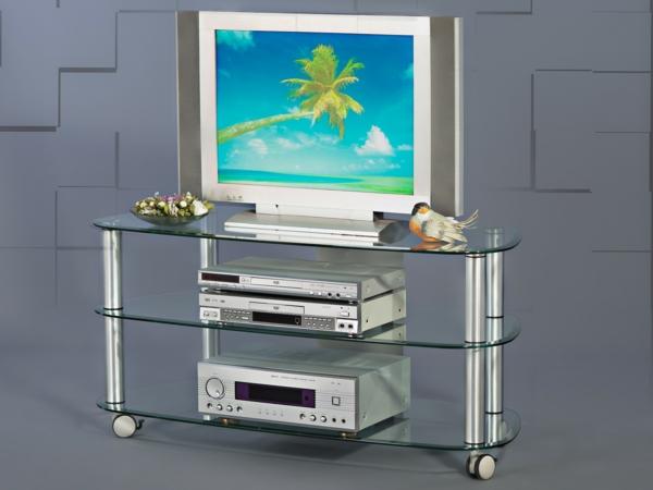 tv-tisch-auf-rollen-graue-wand-dahinter- eine palme auf dem schirm