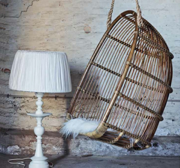vintage-korbhängesessel-neben-einer-weißen-lampe