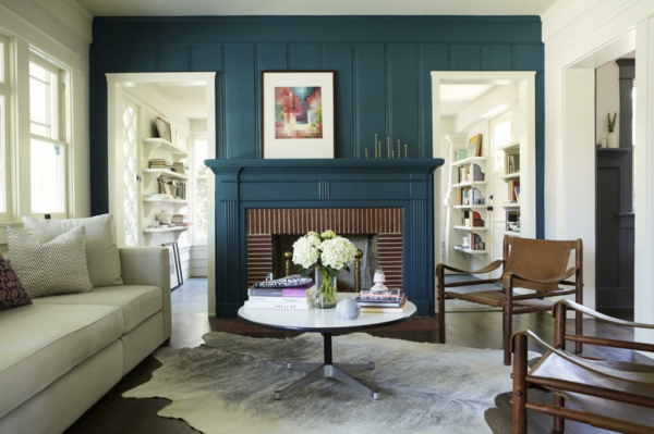 Seating around coffee table in blue panelled living room with animal skin rug