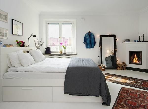 weißes-skandinavisches-schlafzimmer- kamin und großer spiegel