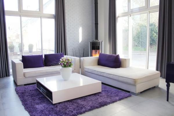 weißes-sofa-mit-sofakissen-in-lila-farbe-gläserne-wände- weicher teppich