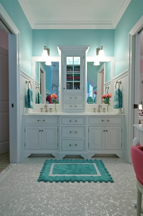 Märchehaftes Badezimmer mit weißen Schränken und türkis Wände und ...