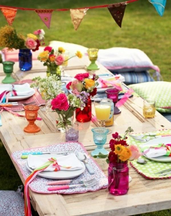 wunderschöne-sommerliche-tischdeko-eine-kreative-idee-bunte blumen und dekokissen auf dem boden