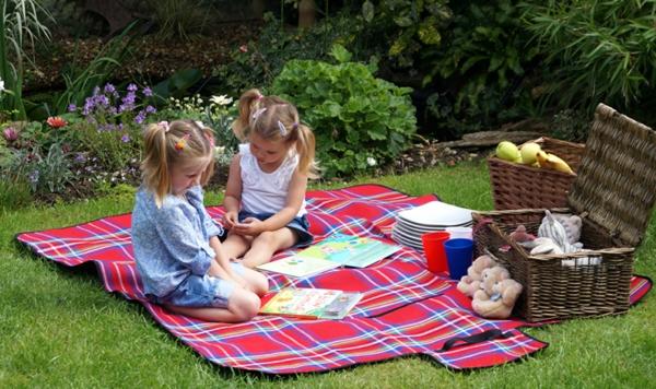 zwei-kleine-mädchen-auf-einer-picknick-decke- sie unterhalten sich