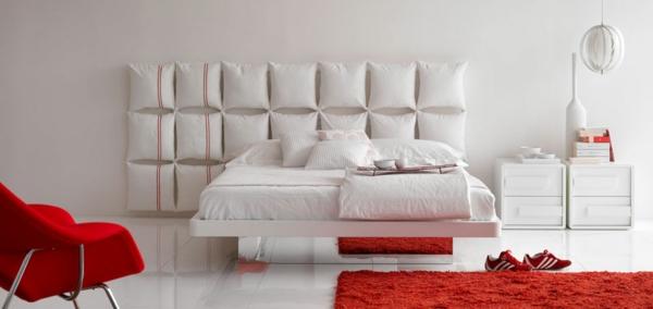 bett-in-weiß-im-schlafzimmer-mit-roten-elementen- dekokissen an der wand