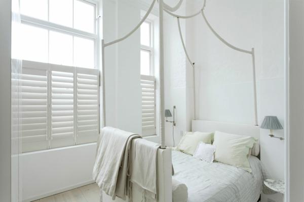 bett-in-weiß-moderne-gestaltung- mit weißen jalousien und gardinen