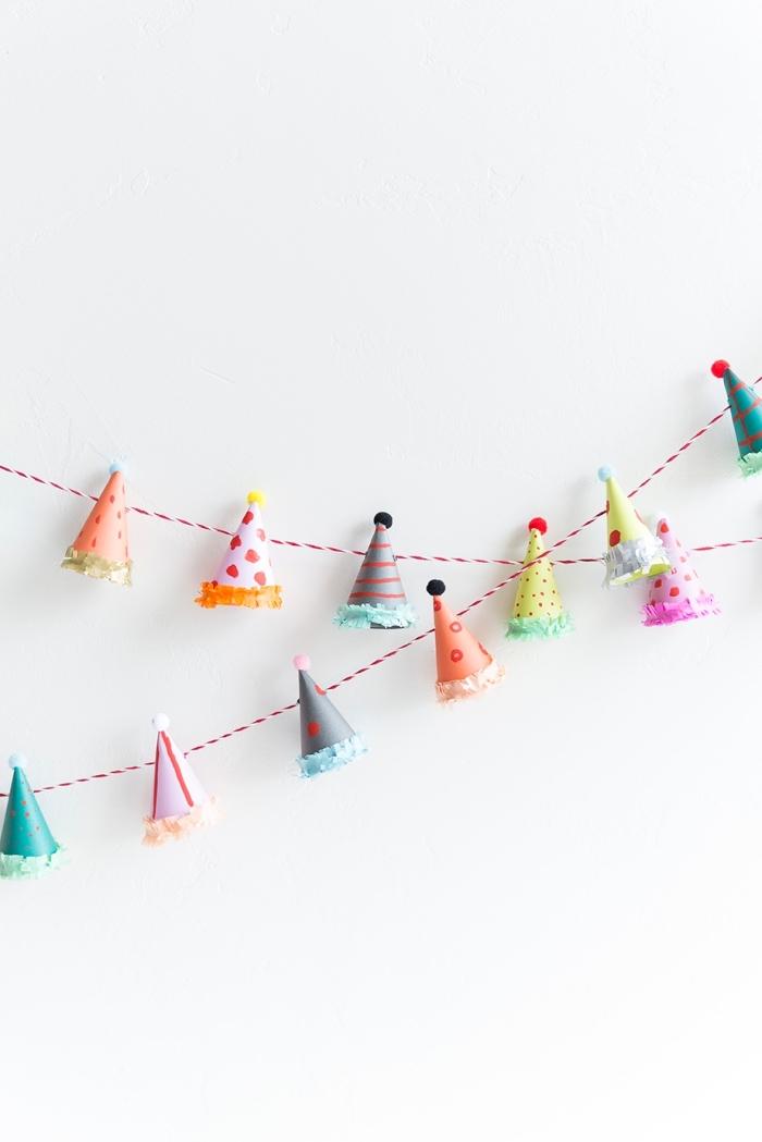deko erster geburtstag, selsbtgemachte girlande mit farbenfrohen partyhüten, wanddeko party