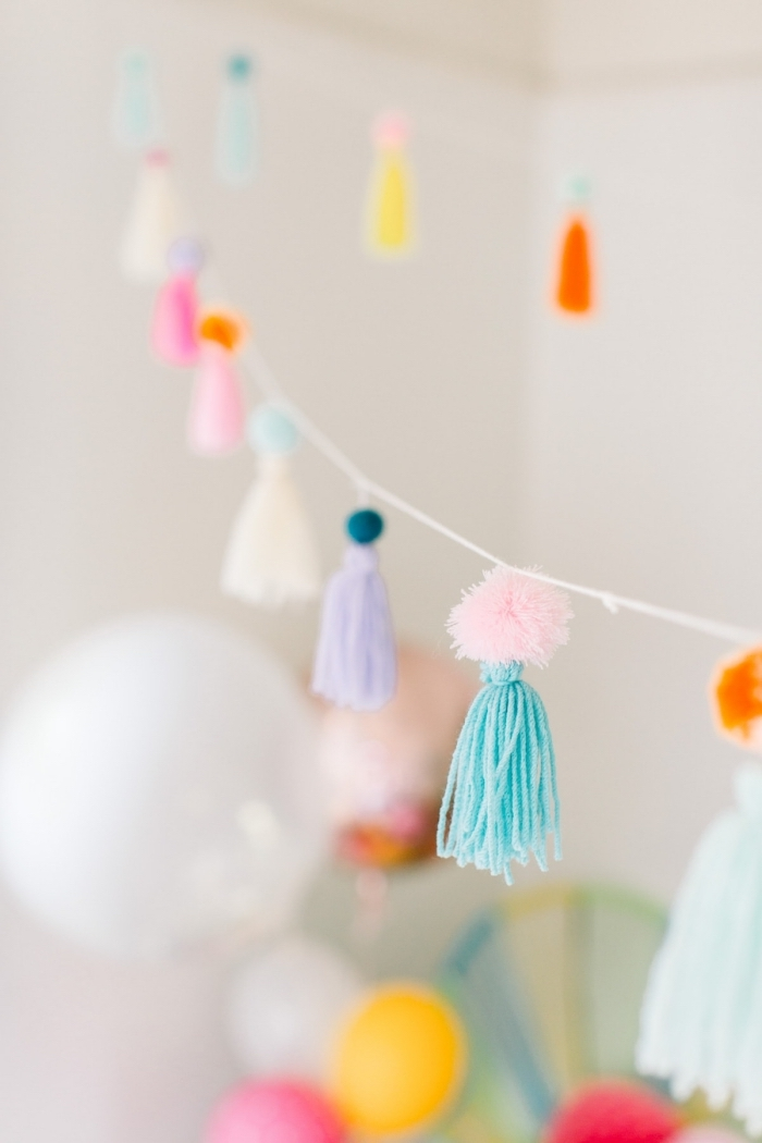 erster geburtstag deko kind, diy girlande aus bunten troddeln aus garn, partydeko