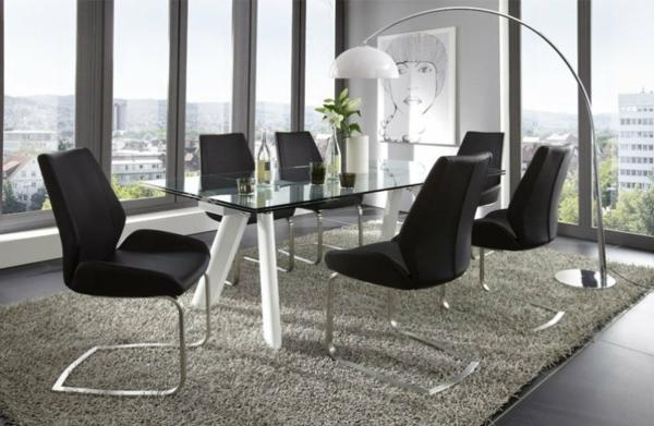 esszimmerstühle-in-schwarz-neben-einem-eleganten-tisch - großer raum und gläserne wände