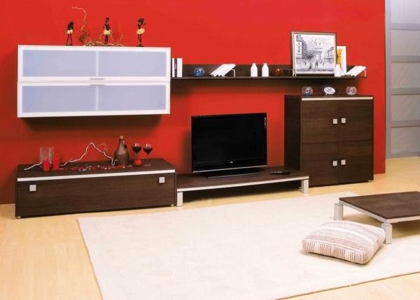 exklusive-tv-möbel-eine-rote-wand-dahinter- und ein kissen auf dem boden