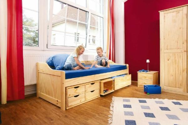 kinderbett-aus-massivholz-mit-schubladen- rote gardinen