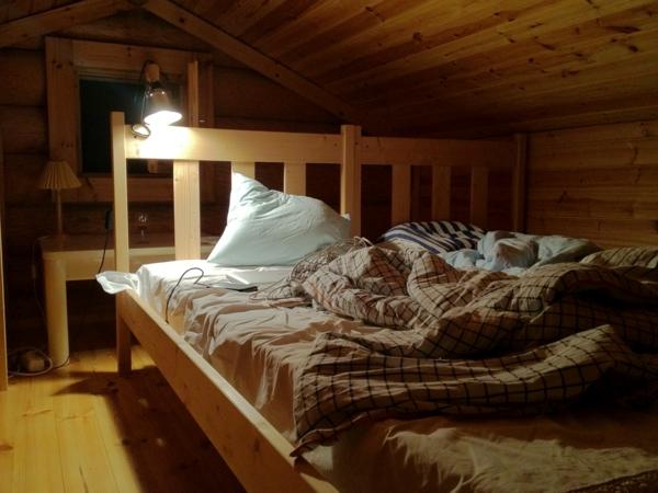leselampe-für-bett-im-hölzernen-schlafzimmer- in einer dachwohnung