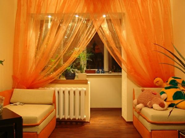 wohnzimmer mit durchsichtigen gardinen in orange - plüschtiere daneben