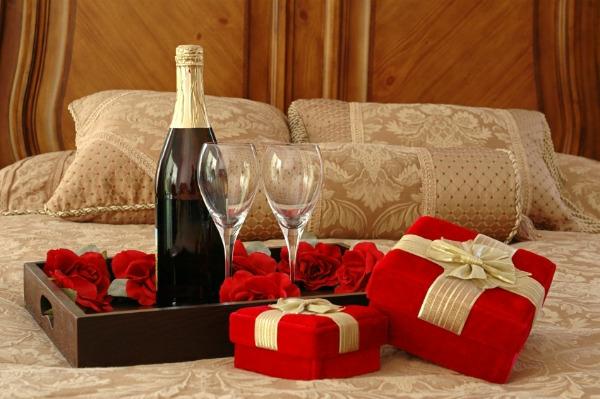 romantik-merkmale-auf-dem-bett-sekt-und-geschenke- sekt mit gläsern