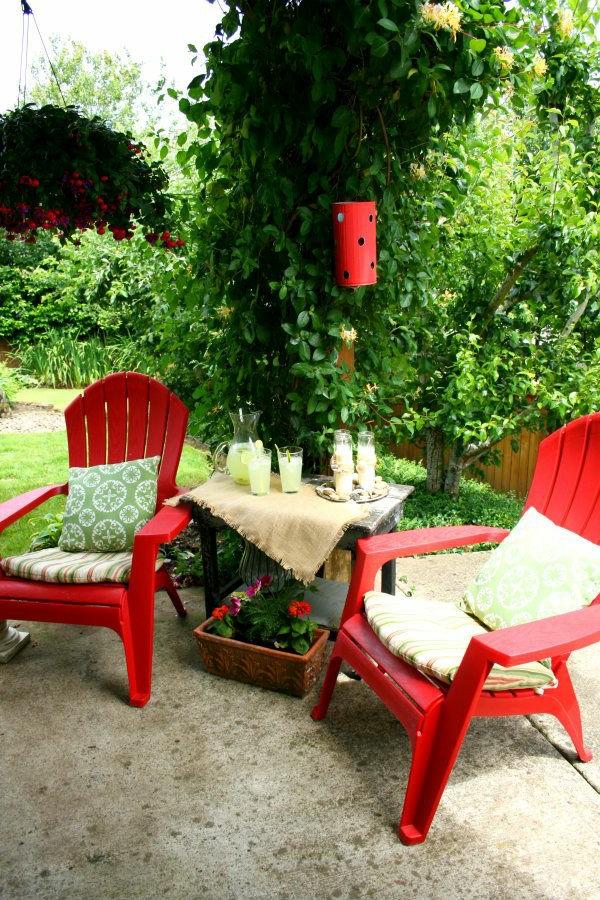 zwei-rote-Stühle-im-Garten-mit-weißen-Sitzkissen