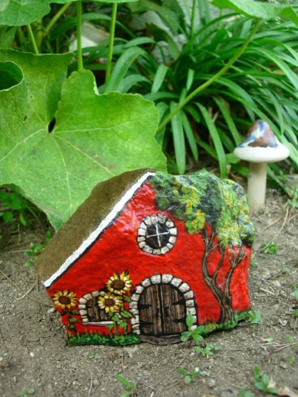 rotes-Haus-und-Baum-verzierte- Steine-als-Dekoration-für-den-Garten