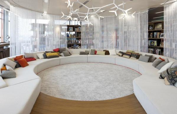 luxuriöses zimmer mit einem großen runden sofa und einem eleganten kronleuchter