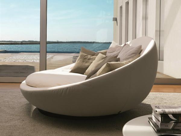 runde-sofas-neues-beige-modell- neben einer glaswand