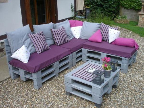schönes-sofa-mit-grauer-gestaltung - viele dekokissen in lila und rosa