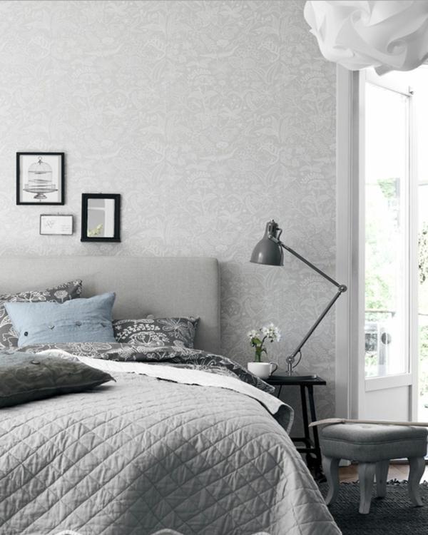 schlafzimmer-in-weiß-und-grau- eine lampe neben dem bett