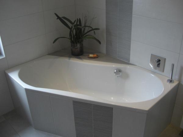 sechseck -badewanne-grau-und-weiß - eine dekopflanze daneben