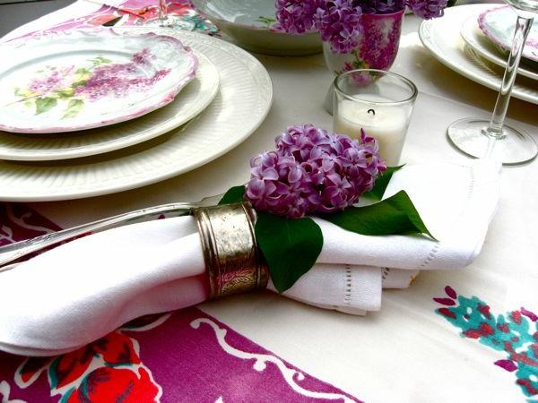 servietten-in-fliederfarben-mit-echten-blumen-dekoriert-eine kerze daneben