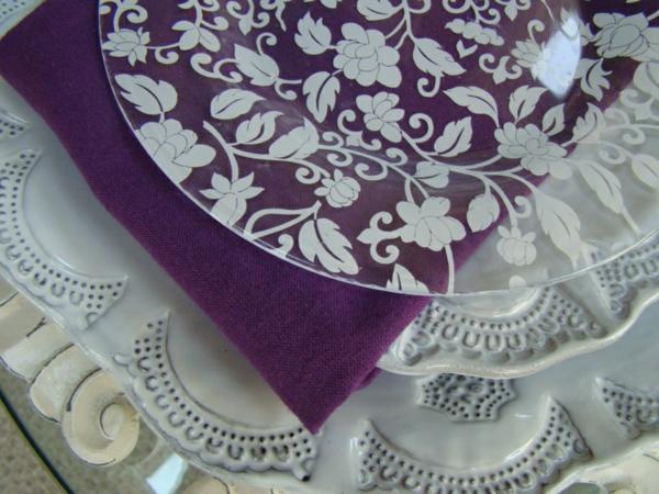 servietten-in-fliederfarben-unter-einem teller aus glas