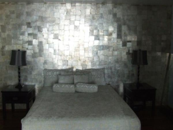silberne-wandfarbe-neben-einem-luxuriösen-bett