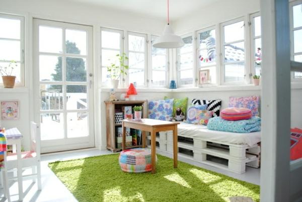 sofa-aus-paletten-im-zimmer-mit-weißer-gestaltung- grüner teppich