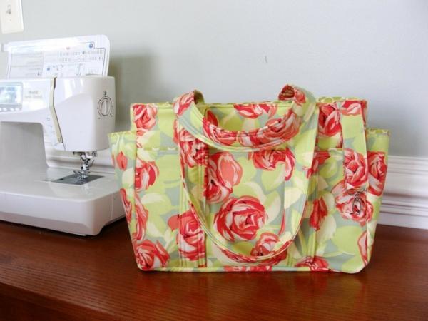 stoffe-mit-rosenmuster-eine-tasche- bunte farben, neben einer nähmaschine