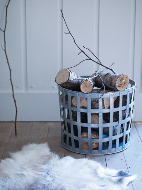 traditioneller-korb-für-kaminholz- im zimmer mit weißen wänden