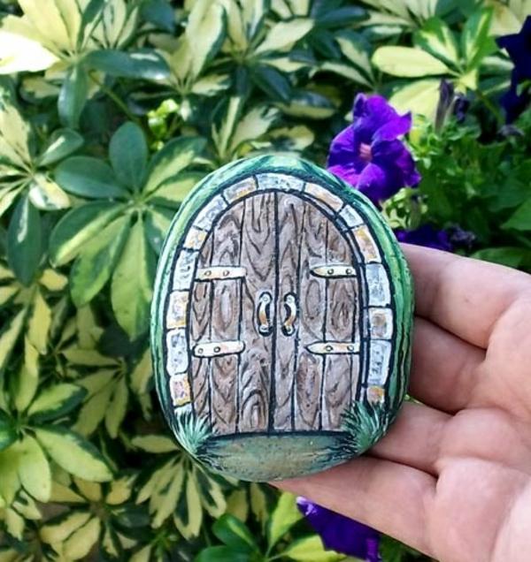 verzierte- Steine-als-Dekoration-für-den-Garten-Holzpforte