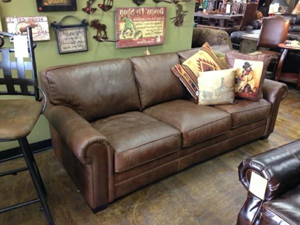 vintage-ledermöbel-ein-braunes-sofa- eine wand mit vielen bildern dahinter
