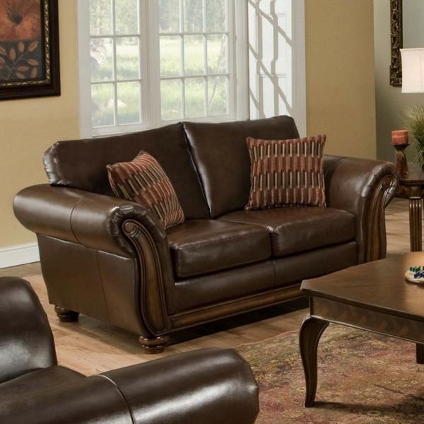 vintage-ledermöbel-eine-couch-mit-braunen-dekokissen- eine glaswand dahinter