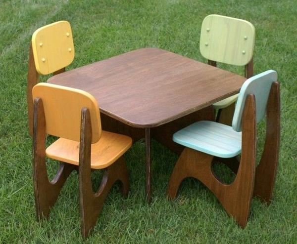 Kindermöbelset-aus-Holz-Tisch-mit-Stühlen-im-Gras